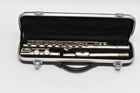 Partial view of a shiny disassembled silver flute in a black case. Studio photo on white background