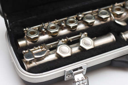 Open case with a flute lying in it with large keys close-up