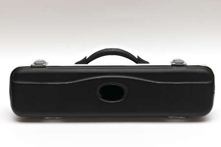 Black long case with locks and a handle for a wind musical instrument on a white background