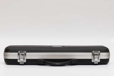 Small long black suitcase with locks for flute on a white background