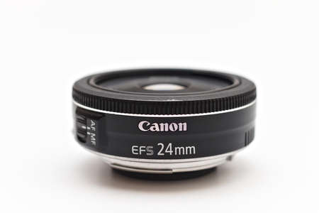 Kiev, Ukraine - March 05th, 2021: Canon EF-S 24 mm STM lens for digital SLR crop cameras with the lens facing up. Close up studio photo in soft light