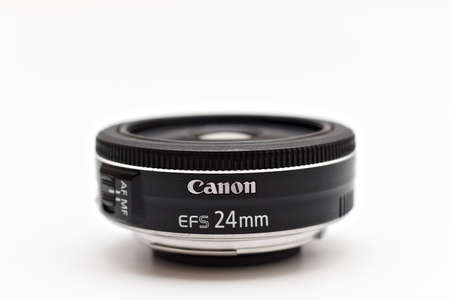Canon EF-S 24 mm STM lens for digital SLR crop cameras with the logo facing forward. Close up studio photo in soft light 報道画像