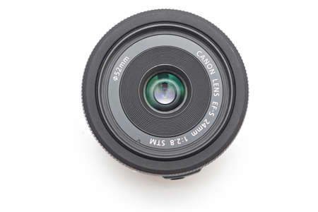 Kiev, Ukraine - March 05th, 2021: Pancake lens Canon EF-S 24 mm STM, front glass up. Top view on white background Editoriali