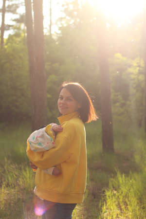 A beautiful young mother with straight hair and in a yellow sweatshirt holds a small child in her arms in the forest in the glare of the evening sunset