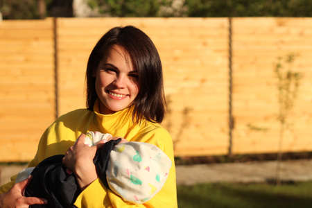 A lovely young mother with straight brown hair and in a yellow sweatshirt holds a small child in her arms in the park in the rays of a sunset