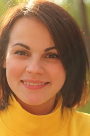 Close-up portrait of a young beautiful girl with straight brown hair and a yellow sweatshirt on a green background outdoors
