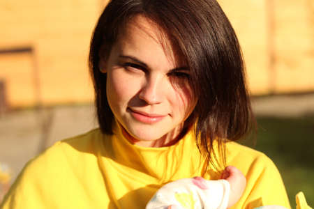 Close-up portrait of a beautiful girl with brown even hair and in a yellow sweatshirt outdoors smiling holding a baby in her arms