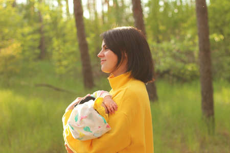 A lovely young mother with straight brown hair and in a yellow sweatshirt holds a small child in her arms in the forest in the rays of a sunny sunset