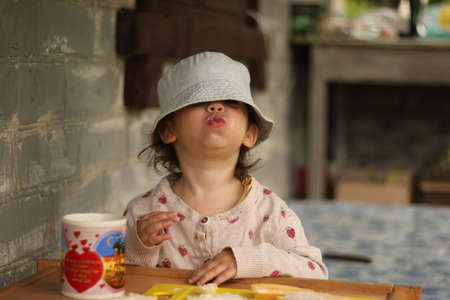 A funny child in a Panama hat and a sweater eats at the table against the background of a brick wall