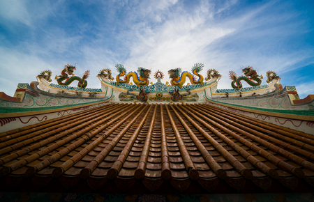 blue dragon: Chinese dragon. - An image of dragon on a roof top of dragon chinese temple. Dragon statue under blue dragon sky. Four dragons. Stock Photo