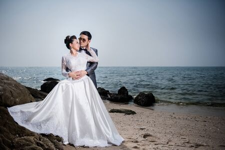 Asian couple wearing wedding dress and suit for beach wedding ceremony. Couple on the beach concept. White bridal dress.