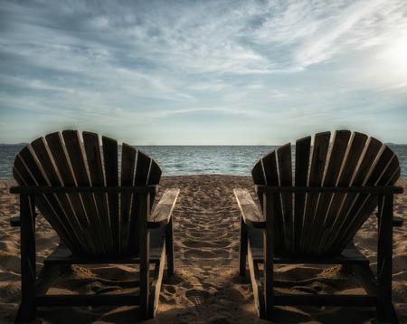 silla de madera: Pareja en silla de playa soleada. Contraste fuerte tono verano. Foto de archivo