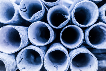 fabricate: Low depth of field image of metal pipe stack in blue shade tone. Rounded iron pipe shape. Stock Photo