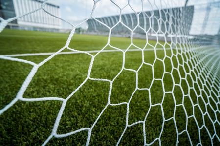 Soccer football net background over green grass and blurry stadium behind Stock Photo