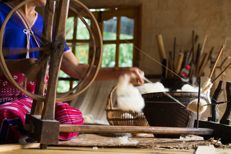 Soft focus image of worker working on traditional loom for wool clothes manufacturing and thread raw material in Chiang Mai, Thailand Stock Photo