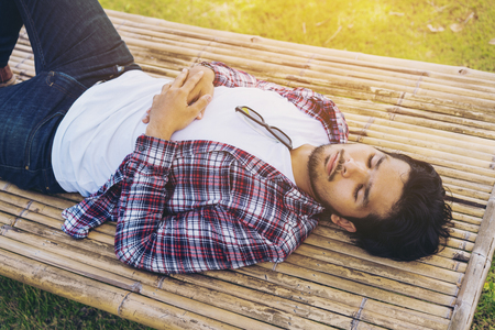 Young man sleep on bamboo bed, seat, table or sunbed made from natural material. Nature, relaxation, and sleep well concept. Daydreamer is daydreaming in day time.