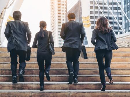 活気のあるビジネス チームは、市内を走るします。ビジネスマンやビジネスウーマンのビジネス建物の背景を持つ完全なビジネス スーツを着てのグ