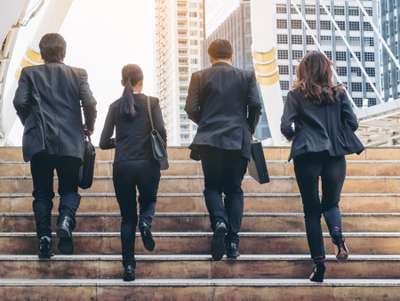 Lively business team running in the city. Group of businessmen and businesswomen wearing full business suit with business buildings background. Teamwork, togetherness, liveliness, business concept.