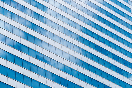 Architecture abstract background. Office building with sky reflection on glass.