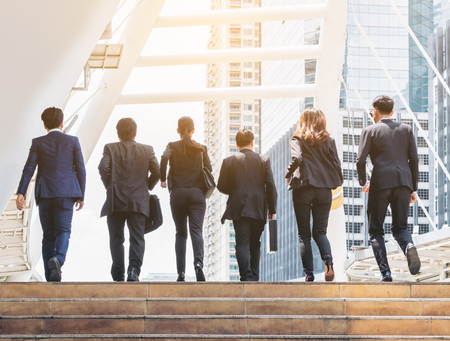 Lively business team walking in the city. Group of businessmen and businesswomen wearing full business suit with business buildings background. Teamwork, togetherness, liveliness, business concept.