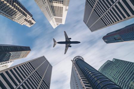 Vliegtuig die over stadsgebouwen vliegen, high-rise bedrijfswolkenkrabbers. Toerisme, transport, transport, reizen per vliegtuig. Vliegtuig transport in het centrum. Rondvliegend vliegtuigvervoer door de stad.