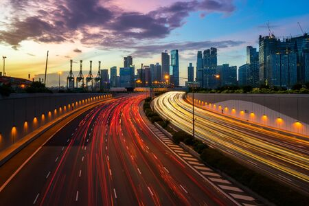 Night city road with traffic headlight motion and city skyline background. Cityscape in Singapore city. Busy road, city and highway in Singapore central area. Light up road by vehicle motion blur. Stock Photo