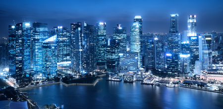 Office buildings background in blue monochrome. Architecture background and office buildings in modern city skyline at night with skyscrapers background over water surface in Marina Bay, Singapore.