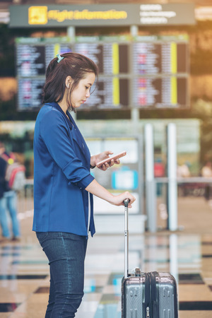 Beautiful young tourist woman with luggage in international airport, near flight information board using smartphone waiting for check-in time