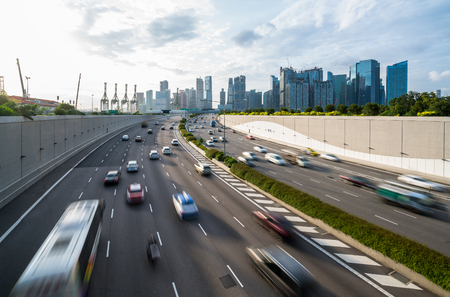 モーション ブラーが適用車、シンガポールの都市高速道路で車でラッシュ時に忙しい道路と都市背景。近代的な建物、背景のオフィス。近代的な都
