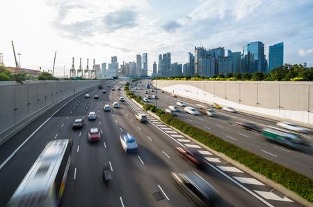 Bezige weg en stadsachtergrond tijdens spitsuur met motie-vaag voertuig, auto in de stadsweg van Singapore. Moderne gebouwen, kantoor op achtergrond. Moderne stad, transport achtergrond concept.