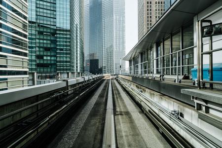 Vooraanzicht van trein in moderne stad. Recht spoor met de achtergrond van stadsgebouwen. Vervoer per trein en spoorweg concept.