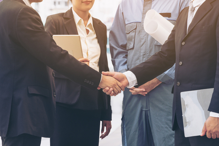 architect drawing: Business man handshake with engineer, secretary in background. Success in engineering project. Architectural project achievement . Construction engineering project agreement. Business people engineer.
