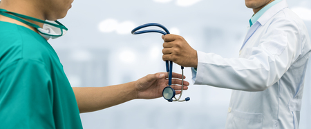 further: Doctor passing stethoscope to surgeon. Concept of specialist referral patients from general practitioner GP for further medication. Web banner design. Stock Photo