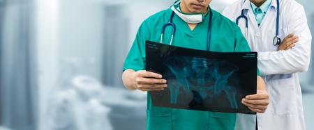 Dokter en chirurg onderzoeken röntgenfilm en diagnosticeren het letsel aan de taillebot van de patiënt. Operatie operatie en medisch spandoekontwerp.