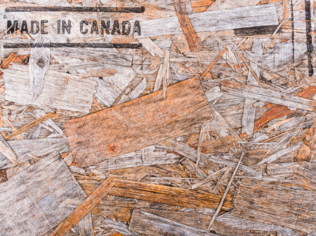 Made in Canada text on recycled wood board background. Recycled compressed wood chippings board background.