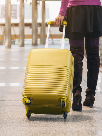 map case: Woman traveller with travel bag or luggage walking in airport terminal walkway for travel abroad. Stock Photo