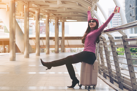 Happy woman traveller in airport walkway with travel bag or luggage. Concept of woman happy travel lifestyle.