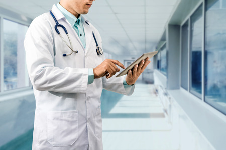 Male doctor working on computer tablet. Concept of medical data analysis by doctors.