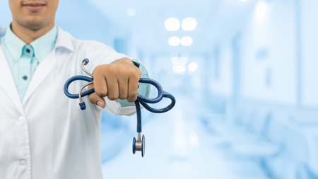 Male doctor holding stethoscope, smiling on hospital background. Healthcare service, general practice doctor and medical career concept.