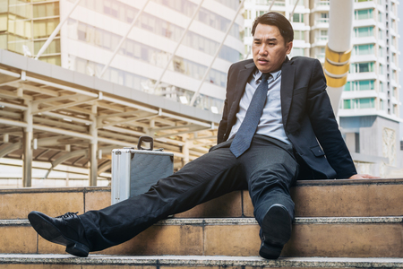 Desperate businessman sitting hopelessly on stair floor in central business district. Concept of business failure, desperation, unemployment in businesses, business depression. Lost businessman fired. Banque d'images