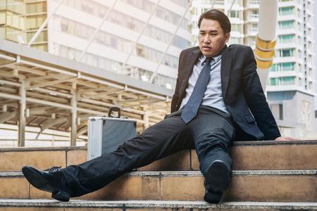 Wanhopige zakenman hopeloos zitten op de trap in het centrale zakenwijk. Concept van bedrijfsfalen, wanhoop, werkloosheid in bedrijven, bedrijfsdepressie. Verloren zakenman ontslagen.