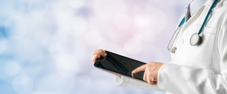 Mannelijke arts die tabletcomputer met behulp van om het geduldige rapport van gezondheidsgegevens te analyseren, die zich op het ziekenhuisachtergrond bevinden. Medische technologie concept.