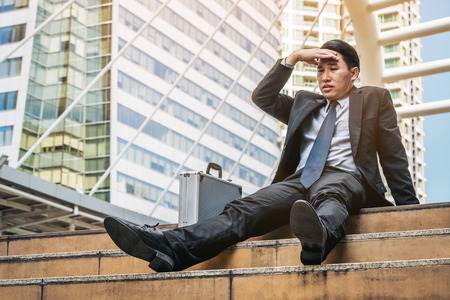 Desperate businessman sitting hopelessly on stair floor in central business district due to unemployment. Concept of failure, desperation, unemployment and business depression.
