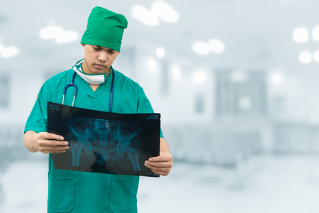 Surgical doctor examining xray film, diagnose patient s waist bone. Surgery operation concept. Stock Photo