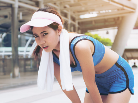 Exhausted woman runner taking breath after hard running exercise session. Concept of healthy woman lifestyle, woman running or jogging and self challenge.