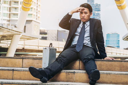 Desperate businessman sitting hopelessly on stair floor in central business district due to unemployment. Concept of failure, desperation, unemployment and business depression. Stock Photo
