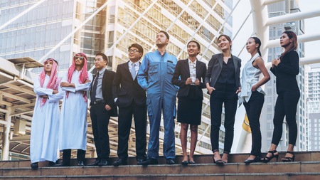Multicultural business people group including Arabic, East Asian, Latin American standing in modern city. Concept of multi ethnic, multiracial business team.