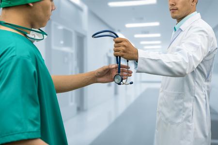 Arts passeren stethoscoop naar chirurg. Concept van gespecialiseerde verwijzende patiënten van huisartsenpraktijk voor verdere medicatie.