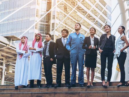 Multiculturele bedrijfsmensengroep met inbegrip van Arabische, Oost-Aziatische, Latijns-Amerikaanse die zich in moderne stad bevinden. Concept van multi-etnische, multiraciale zakelijke team.