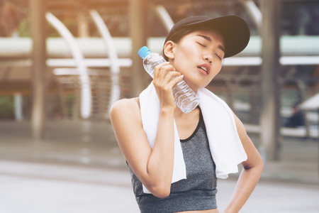 Sport woman with drinking water bottle is tired after running exercise on hot summer day. Concept of healthy lifestyle by drinking water. Stock Photo